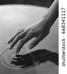 hand touching water | Shutterstock . vector #668341117