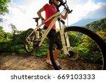woman cyclist carrying mountain ... | Shutterstock . vector #669103333