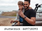 father with little boy using... | Shutterstock . vector #669718393