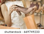 Small photo of Cropped close up of a woman stealing shoes at the store putting high heels into her shopping bag shoplifting crime thief shoplifter retail criminal poverty poor concept.