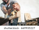 a young brunette man builder in ... | Shutterstock . vector #669935227