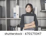 asian woman holding document at ... | Shutterstock . vector #670175347