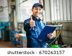 smiling mechanic thumbs up | Shutterstock . vector #670263157
