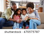family sitting on sofa in... | Shutterstock . vector #670575787