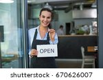 woman holding open sign in cafe  | Shutterstock . vector #670626007