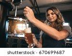 Young woman dispensing beer in...