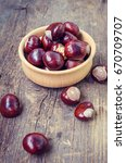 Small photo of Fresh chestnuts in a bowl on an old wooden table. Group of chestnuts. Chestnuts - fruits horse chestnut - Aesculus hippocastanum. Dark background. Autumn background. Selective focus.