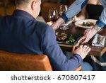 positive young waiter serving... | Shutterstock . vector #670807417