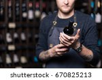 focused young male sommelier in ... | Shutterstock . vector #670825213