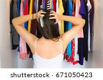 Small photo of Frustrated woman standing in front of her closet, trying to find something to wear