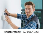 handsome young electrician... | Shutterstock . vector #671064223