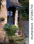 Small photo of Partial View of a Traditional Ageless Sandstone Cottage with French Window, Timeless Awning & Pot Plants.