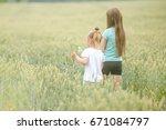 sisters walking through field ...   Shutterstock . vector #671084797