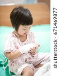 Small photo of 3-4 years old asian girl admitted to the hospital / She is sick about gastrointestinal infections and look at her hand on the saline solution and the disinfectant, wrapped in her hand.