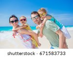 young family of four on beach... | Shutterstock . vector #671583733