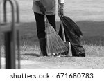 Small photo of Gardener sweep old leaves by broom, clean garden, clear garbage