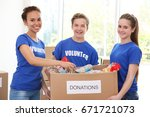 young volunteers with box of... | Shutterstock . vector #671721073