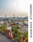 Small photo of A scene at slum area with tiny houses built-in for living with sunset in the background,Adyar,Chennai,India,May 20 2017