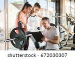 gym instructor assisting two... | Shutterstock . vector #672030307