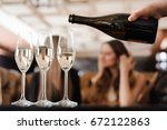 man fills glasses of champagne... | Shutterstock . vector #672122863