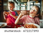 kids eat pizza and pasta at... | Shutterstock . vector #672217393