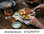 man is eating dinner at a... | Shutterstock . vector #672294757