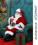 authentic santa clause sitting in large green chair pointing finger - stock photo