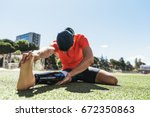 disabled man athlete stretching ... | Shutterstock . vector #672350863