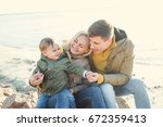 family on a walk by the water.... | Shutterstock . vector #672359413
