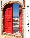 Small photo of Vintage red door ajar and view of patio and blue ocean