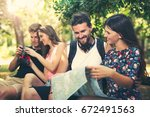 young friends tourists with map ... | Shutterstock . vector #672491563