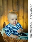 Small photo of Little handsome European-looking boy with an amazed face in a sedentary pose