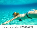 Small photo of Female apnea bikini swims in crystal trapical sea. Underwater scene of a woman snorkeling and doing free diving. Watersport activity in summer vacations. Tropical destination and leisure concept.