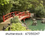 A Red Wooden Bridge Over A Pon...
