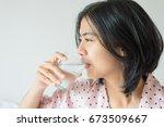 asian woman drinking a glass... | Shutterstock . vector #673509667