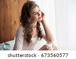 cheerful young lady holding... | Shutterstock . vector #673560577