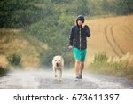 Stock photo young man walking with his dog labrador retriever in heavy rain on the rural road 673611397