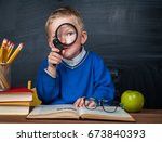 cute clever boy is sitting at a ... | Shutterstock . vector #673840393