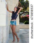 Small photo of Pretty brunette in tan pantyhose and open toe heels flipping hair while leaning on white brick column.