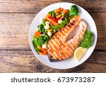 plate of grilled salmon steak... | Shutterstock . vector #673973287