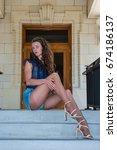 Small photo of Pretty brunette in tan pantyhose and open toe heels showing legs on steps in portrait orientation.