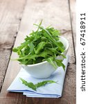 rucola in white bowl on napkin - stock photo