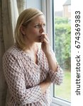Small photo of Sad Woman Suffering From Agoraphobia Looking Out Of Window