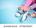 young girl learning to tie her... | Shutterstock . vector #674642467
