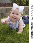 a baby girl laying on the grass ... | Shutterstock . vector #674773447
