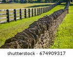 Small photo of A stone fence and a wooden fence line a green pasture In horse country, Lexington, Kentucky, USA