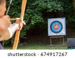 Small photo of archer aiming arrow at sport aim