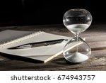 hourglasses and book on a... | Shutterstock . vector #674943757