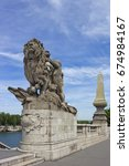 Small photo of Baroque statue of lion on the bridge of Alexander III, which was built across Seine river in XIX century, and is free to use for people and vehicles in Paris, France.