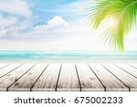 empty wooden table and palm... | Shutterstock . vector #675002233